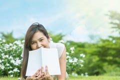 Mujer asiática que miente en campo de hierba con el libro blanco en el parque Fotos de archivo
