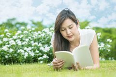 Mujer asiática que miente en el campo de hierba para leer un libro blanco en el parque Foto de archivo libre de regalías