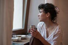 Mujer asiática que mira hacia fuera la ventana y que bebe té Imagen de archivo