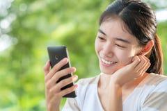 Mujer asiática que mira smartphone Fotos de archivo libres de regalías