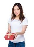 Mujer asiática que muestra con el giftbox Fotos de archivo libres de regalías