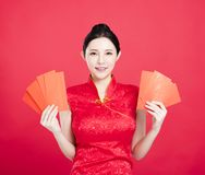 Mujer asiática que muestra el sobre rojo Imagenes de archivo