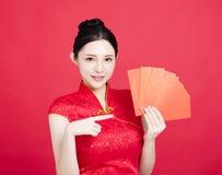 Mujer asiática que muestra el sobre rojo Fotos de archivo