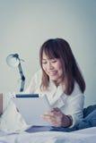 Mujer asiática que pone en piso con la tableta Imagen de archivo libre de regalías