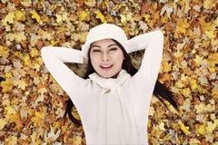 Mujer asiática que pone feliz en las hojas de otoño Imagenes de archivo