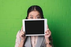 mujer asiática que presenta la tableta digital imagen de archivo