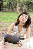 Mujer asiática que señala por medio de una bandera con la computadora portátil que se sienta en el parque Imágenes de archivo libres de regalías