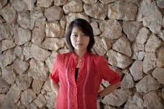Mujer asiática que se coloca en la fuente de la pared de la roca Imagen de archivo libre de regalías