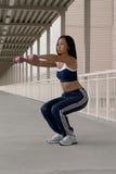 Mujer asiática que se pone en cuclillas con pesas de gimnasia fotos de archivo