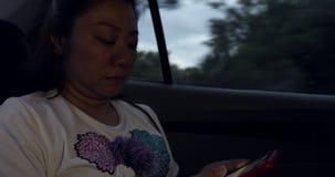 Mujer asiática que se sienta en asiento de carro y que juega en el teléfono elegante mientras que teniendo un paseo en asiento tr metrajes