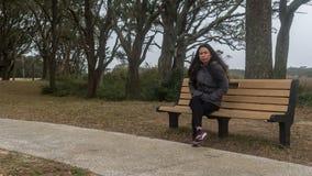 Mujer asiática que se sienta en banco en parque foto de archivo libre de regalías