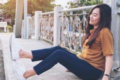Mujer asiática que se sienta en el puente con la cara sonriente y que siente feliz Fotografía de archivo libre de regalías