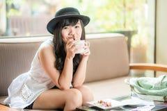Mujer asiática que se sienta en el sofá con café Fotografía de archivo