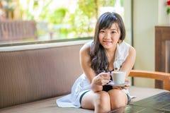Mujer asiática que se sienta en el sofá con café Imágenes de archivo libres de regalías