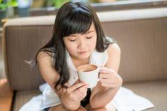 Mujer asiática que se sienta en el sofá con café Fotos de archivo libres de regalías