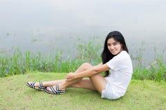 Mujer asiática que se sienta en la hierba Fotos de archivo libres de regalías