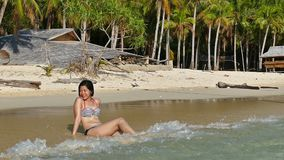 Mujer asiática que se sienta en la playa tropical hermosa metrajes