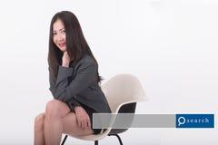 Mujer asiática que se sienta en la silla con el gráfico del Search Engine Imagen de archivo