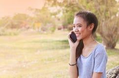 Mujer asiática que se sienta en piedra usando un teléfono móvil Fotografía de archivo libre de regalías