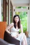Mujer asiática que se sienta en silla Foto de archivo libre de regalías