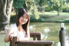 Mujer asiática que se sienta en un banco de madera Imagen de archivo