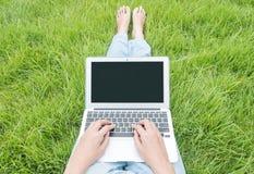 Mujer asiática que sienta en piso de la hierba en el fondo texturizado jardín para el uso un ordenador portátil, concepto del tra Fotos de archivo libres de regalías