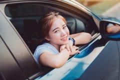 Mujer asiática que sonríe con el viaje en coche de la ventana trasera que conduce vacaciones de verano del viaje por carretera foto de archivo