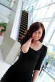 Mujer asiática que sonríe en el edificio moderno Foto de archivo libre de regalías