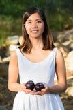 Mujer asiática que sonríe mientras que sostiene ciruelos Imagen de archivo