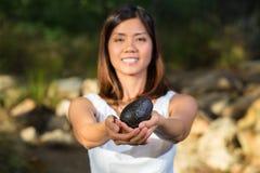 Mujer asiática que sostiene el aguacate Imagenes de archivo
