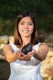 Mujer asiática que sostiene el aguacate Fotografía de archivo