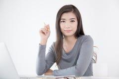 Mujer asiática que sostiene el lápiz amarillo disponible y que usa el ordenador portátil, Femal Imágenes de archivo libres de regalías