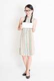 Mujer asiática que sostiene la tarjeta de papel en blanco blanca Imágenes de archivo libres de regalías
