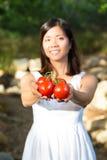 Mujer asiática que sostiene los tomates rojos Fotografía de archivo libre de regalías