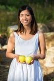 Mujer asiática que sostiene manzanas verdes Foto de archivo libre de regalías