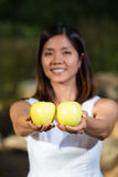 Mujer asiática que sostiene manzanas verdes Foto de archivo