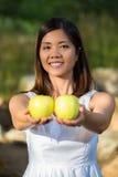 Mujer asiática que sostiene manzanas verdes Fotos de archivo libres de regalías