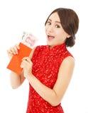 Mujer asiática que sostiene un sobre rojo con el dinero Imagenes de archivo