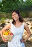 Mujer asiática que sostiene una cesta de paprikas y de mango Fotografía de archivo libre de regalías