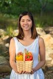 Mujer asiática que sostiene una cesta de paprikas y de mango Imágenes de archivo libres de regalías
