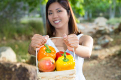 Mujer asiática que sostiene una cesta de paprikas y de mango Foto de archivo