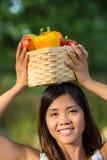Mujer asiática que sostiene una cesta de paprikas y de mango Imagen de archivo libre de regalías