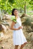 Mujer asiática que sostiene una flor blanca Fotos de archivo libres de regalías
