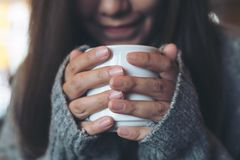 Mujer asiática que sostiene y que bebe el café caliente en invierno imagen de archivo libre de regalías