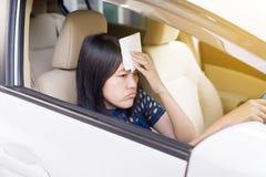 Mujer asiática que tiene caliente porque una ola de calor en su coche imagen de archivo