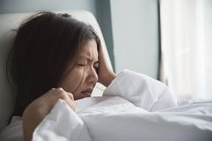 Mujer asiática que tiene dolor de cabeza en su cama jaqueca Enfermedad, disea Imagenes de archivo
