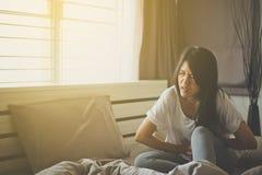 Mujer asiática que tiene dolor de estómago doloroso en cama Imagenes de archivo