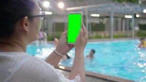 Mujer asiática que toma la imagen con la pantalla verde en teléfono elegante almacen de video