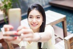Mujer asiática que toma un selfie con su teléfono en foco del parque público Imágenes de archivo libres de regalías