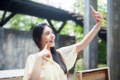 Mujer asiática que toma un selfie con su teléfono en parque público Imagenes de archivo